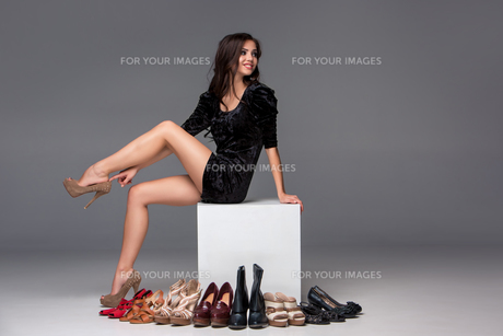 picture of sitting woman trying on high heeled shoesの写真素材 [FYI00647918]