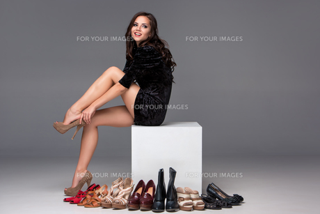 picture of sitting woman trying on high heeled shoesの写真素材 [FYI00647919]