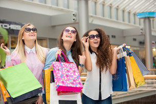 three beautiful girls in sunglasses with shopping bagsの写真素材 [FYI00647957]
