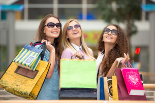 three beautiful girls in sunglasses with shopping bagsの写真素材 [FYI00647960]