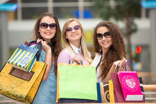 three beautiful girls in sunglasses with shopping bagsの写真素材 [FYI00647962]
