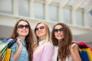 three beautiful girls in sunglasses with shopping bagsの写真素材 [FYI00647965]