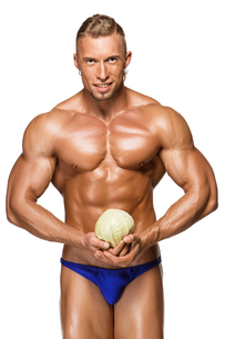 Shaped and healthy body man holding a fresh cabbage ,  isolated on white backgroundの写真素材 [FYI00647978]