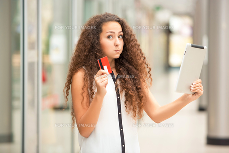 Beautiful young girl paying by credit card for shoppingの写真素材 [FYI00648056]
