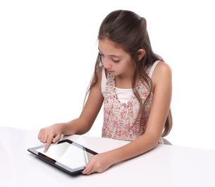 Beautiful pre-teen girl using a tablet computerの写真素材 [FYI00648154]