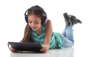 Beautiful pre-teen girl on the floor, usin a tablet computer and headphonesの写真素材 [FYI00648160]