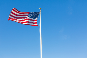 American flag against blue skyの写真素材 [FYI00648207]