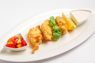 Fried fish in batter with sauce, lemon and vegetablesの写真素材 [FYI00648638]