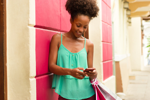 African American Girl Shopping And Text Messaging On Phoneの写真素材 [FYI00648731]