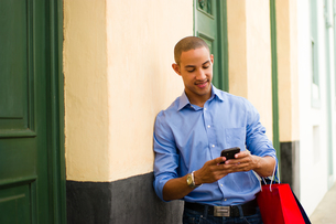 African American Man Shopping And Text Messaging On Phoneの写真素材 [FYI00648733]