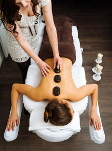 Massage therapist applying a hot stone massageの写真素材 [FYI00648801]