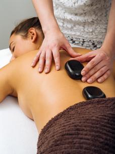 Massage therapist placing the hot stonesの写真素材 [FYI00648804]