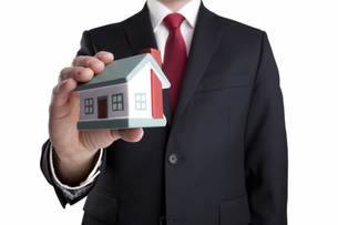 Businessman with house miniature in hand isolated on whiteの写真素材 [FYI00648890]