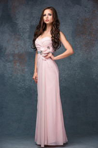 Beautiful young brunette woman with her hair posing in a i long pink dress. Studio, on gray backgroundの写真素材 [FYI00649433]