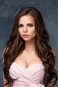 Beautiful young brunette woman with her hair posing in a pink dress. Studio, on gray backgroundの写真素材 [FYI00649434]