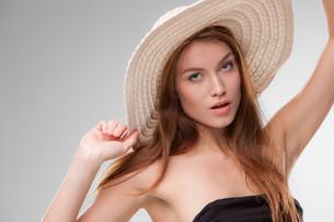 Beautiful girl with hat posing in studioの写真素材 [FYI00649590]