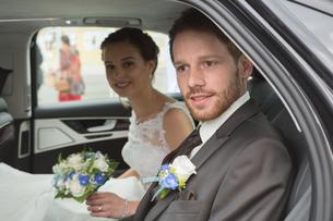 bridal couple sitting in the wedding carの写真素材 [FYI00649612]