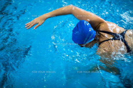 Female swimmer in an indoor swimming pool - doing crawl (shallow DOF)の写真素材 [FYI00650194]