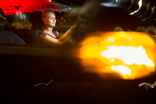 Driving a car at night - pretty, young woman driving her modern car at night in a city (shallow DOF  color toned image)の写真素材 [FYI00650197]