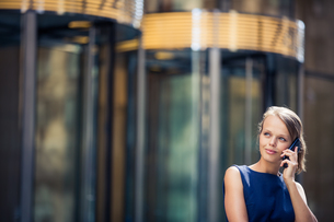Gorgeous young businesswoman calling on her phone in front of her company's building (shallow DOF  color toned image)の写真素材 [FYI00650213]