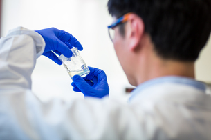 Male researcher carrying out research in a chemistry lab (color toned image  shallow DOF)の写真素材 [FYI00650214]