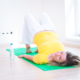 Pretty young woman doing YOGA exercise at homeの写真素材 [FYI00650219]