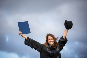 Pretty, young woman celebrating joyfully her graduation - spreading wide her arms, holding her diploma, savouring her success (color toned image  shallow DOF).の写真素材 [FYI00650220]