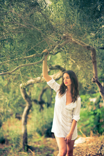 Attractive, young brunette on the beach, amid olive trees, looking both sensual and naturalの写真素材 [FYI00650246]