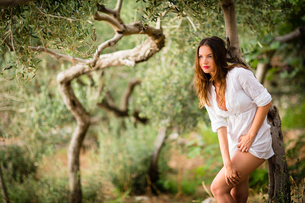 Attractive, young brunette on the beach, amid olive trees, looking both sensual and naturalの写真素材 [FYI00650249]