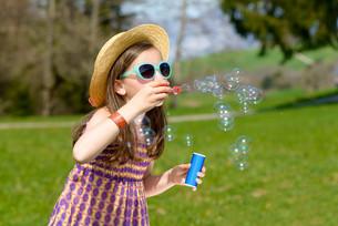 a little girl making soap bubblesの写真素材 [FYI00650498]