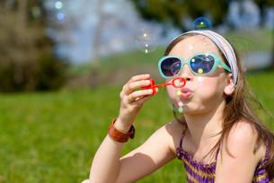 a little girl making soap bubblesの写真素材 [FYI00650502]