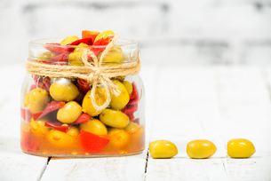 glass jar with olives and peppers on white tableの写真素材 [FYI00650563]