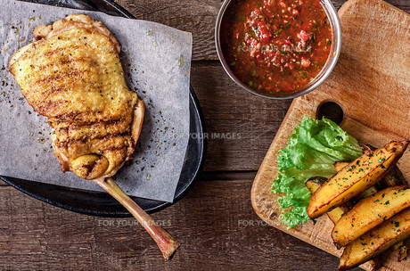 Fried chicken meat on the bone, potato wedges, lettuceの写真素材 [FYI00650755]