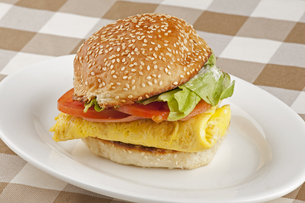 A delicious breakfast of eggs, ham, lettuce, and sliced tomatoesの写真素材 [FYI00651425]