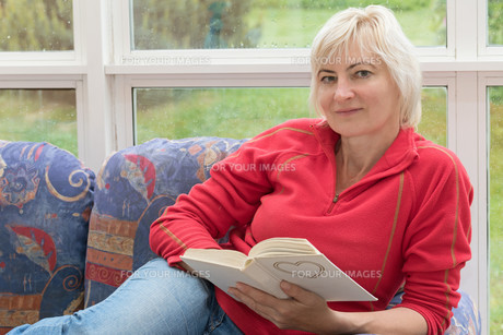 Blonde middle-aged woman is relaxing with a book in her handsの写真素材 [FYI00651551]