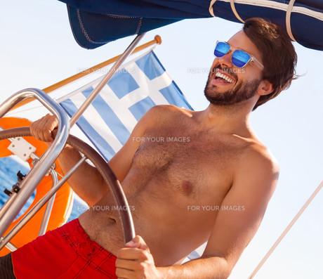 Handsome man driving sailboatの写真素材 [FYI00651575]