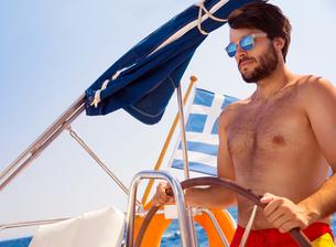 Handsome man driving sailboatの写真素材 [FYI00651576]