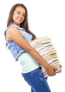 young student girl holding a stack of booksの写真素材 [FYI00651634]