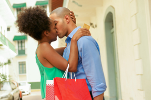 African American Couple Shopping With Credit Card Kissingの写真素材 [FYI00651979]