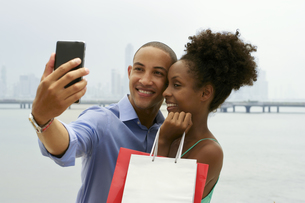 African American Couple Shopping Taking Selfie With Mobile Phoneの写真素材 [FYI00651982]