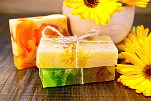 Soap homemade with calendula and mortar on boardの写真素材 [FYI00652640]
