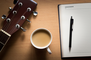 hot coffee with guitar and notepad on table break time for thinking ideaの写真素材 [FYI00652755]