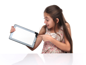 Beautiful pre-teen girl showing a tablet computer.の写真素材 [FYI00652941]