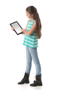 Beautiful pre-teen girl using a tablet computerの写真素材 [FYI00652951]
