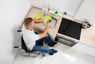 Disabled Man With Sponge Washing Dishesの写真素材 [FYI00653366]