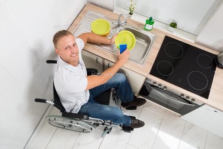 Man On Wheelchair With Sponge Washing Dishesの写真素材 [FYI00653370]