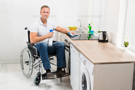 Man On Wheelchair Cleaning Induction Stoveの写真素材 [FYI00653372]