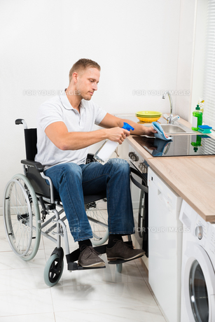 Handicapped Man Cleaning Induction Stoveの写真素材 [FYI00653374]