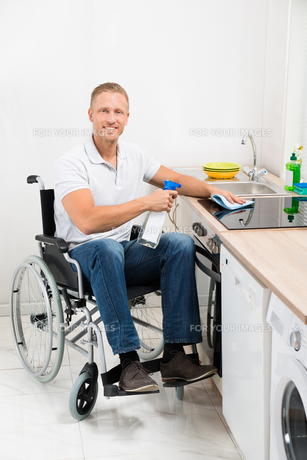 Man On Wheelchair Cleaning Induction Stoveの写真素材 [FYI00653376]