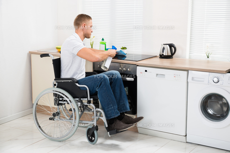 Handicapped Man Cleaning Induction Stoveの写真素材 [FYI00653378]